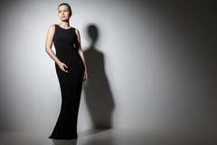 美丽的妇女式样摆在典雅的黑色 图库摄影