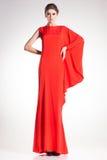 美丽的妇女式样摆在简单的典雅的红色礼服 免版税库存图片