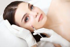 美丽的妇女得到在她的面孔的射入。整容外科 库存照片