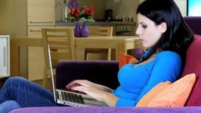 美丽的妇女微笑的在家与计算机一起使用 股票视频