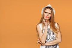 年轻美丽的妇女想法的注视着对边空白的拷贝空间,在橙色背景 库存图片