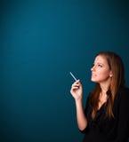美丽的妇女抽烟的香烟vith复制空间 免版税库存照片