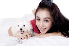 美丽的妇女拥抱她的在床上的狗 图库摄影
