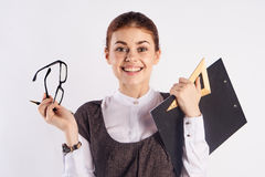 年轻美丽的妇女拿着玻璃和文件在白色背景,画象,老师,微笑 免版税图库摄影