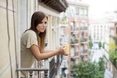美丽的妇女放松了快乐的饮用的茶咖啡在公寓阳台大阳台 库存照片