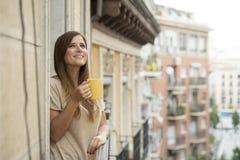美丽的妇女放松了快乐的饮用的茶咖啡在公寓阳台大阳台 免版税库存照片