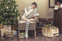 美丽的妇女放松的坐在圣诞节int的一把椅子 库存图片