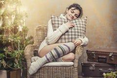 美丽的妇女放松的坐在圣诞节int的一把椅子 免版税库存照片