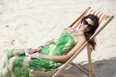 美丽的妇女放松的说谎在太阳懒人 免版税库存照片