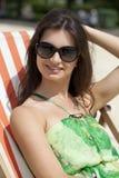 美丽的妇女放松的说谎在太阳懒人 库存图片