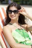 美丽的妇女放松的说谎在太阳懒人 库存照片