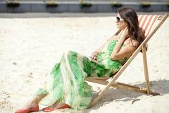 美丽的妇女放松的说谎在太阳懒人 免版税库存图片
