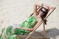 美丽的妇女放松的说谎在太阳懒人 免版税图库摄影