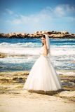 年轻美丽的妇女新娘室外画象婚礼礼服的在海滩 免版税库存照片