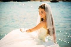 年轻美丽的妇女新娘室外画象婚礼礼服的在海滩 免版税库存图片