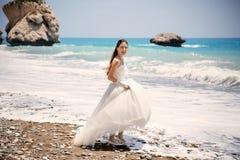 年轻美丽的妇女新娘室外画象婚礼礼服的在海滩 Petra tou Romiou -美之女神的岩石 免版税库存图片