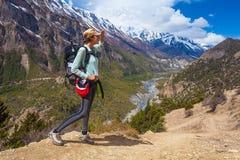 美丽的妇女旅客背包徒步旅行者山道路 女孩看起来正确的方式并且采取RestNorth夏天雪风景 免版税库存照片