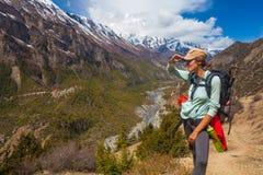 美丽的妇女旅客背包徒步旅行者山道路 女孩神色天际采取RestNorth夏天风景背景 免版税图库摄影