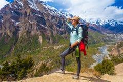 美丽的妇女旅客背包徒步旅行者山道路 看起来正确的方式的女孩和采取RestNorth夏天雪 免版税库存图片