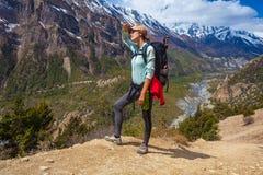 美丽的妇女旅客背包徒步旅行者山道路 看起来顶面小山的女孩和采取RestNorth夏天雪风景 免版税库存图片