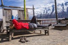 美丽的妇女旅客背包徒步旅行者采取休息山大阳台村庄 女孩睡觉长凳 北部雪峰顶 库存图片