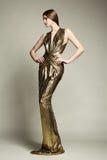 年轻美丽的妇女时尚画象金礼服的 库存照片