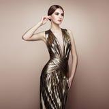 年轻美丽的妇女时尚画象金礼服的 免版税库存图片