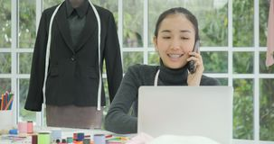 美丽的妇女时装设计师在谈话她的书桌坐电话 股票录像