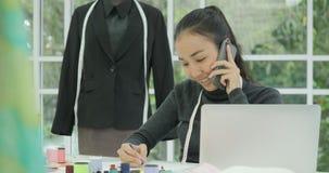 美丽的妇女时装设计师画象在谈话她的书桌坐电话 影视素材