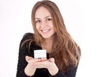 美丽的妇女显示她的面霜 免版税库存图片