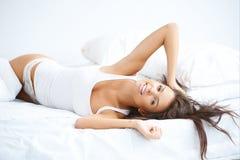 美丽的妇女有一懒惰天在床 免版税库存照片