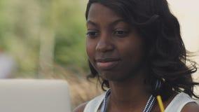 美丽的妇女有在便携式计算机outsite的录影闲谈在城市 库存照片