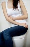 美丽的妇女有stomachache在她的卫生间在家 库存图片