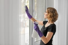 美丽的妇女清洁窗口 免版税图库摄影