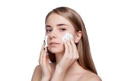 美丽的妇女清洁面孔有泡沫治疗光背景 库存图片