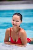 美丽的妇女游泳池手段轻松的画象年轻亚洲女孩愉快的微笑热带假期 免版税库存照片