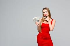 美丽的妇女演播室画象红色礼服的在哪里拿着金钱,认为花费它 年轻苗条女孩与 免版税库存照片
