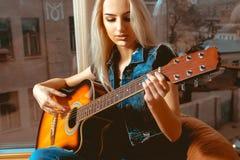 美丽的妇女特写镜头照片有吉他的在她的手上 免版税库存照片
