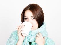 美丽的妇女特写镜头画象一份羊毛围巾、饮用的热的茶或者咖啡的从白色杯子 免版税库存照片
