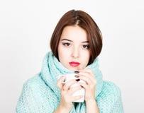 美丽的妇女特写镜头画象一份羊毛围巾、饮用的热的茶或者咖啡的从白色杯子 免版税库存图片