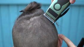 美丽的妇女理发师剪在客户的项的头发有电剃刀飞剪机和梳理视图关闭的 影视素材