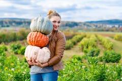 美丽的妇女用在农场的三个巨大的南瓜 免版税库存照片