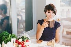 年轻美丽的妇女用短发饮用的通入蒸汽的咖啡 免版税库存照片