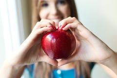 美丽的妇女用红色苹果在家 库存图片