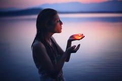 美丽的妇女由蜡烛在紫色湖水域中点燃了 免版税库存照片