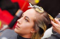 美丽的妇女画象一个发廊的与一根美发师切口客户` s头发在被弄脏的背景中 库存图片
