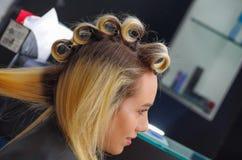 美丽的妇女画象一个发廊的与美发师与在头的卷发的人一起使用,在发廊背景中 库存照片