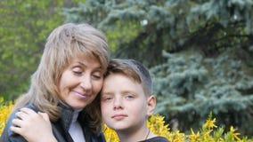 美丽的妇女画象在与轻轻地微笑白发和的蓝眼睛的几年看她青少年的儿子和 影视素材