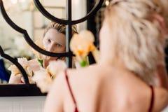 美丽的妇女画象有花的在室内镜子附近 免版税库存照片
