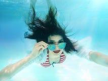 美丽的妇女画象水下与太阳镜 免版税库存照片